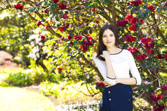 Young beautiful woman with long straight dark hair posing in spr. Ing garden Royalty Free Stock Photo