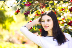 Young beautiful woman with long straight dark hair posing in spr. Ing garden Stock Image
