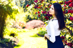 Young beautiful woman with long straight dark hair posing in spr. Ing garden Stock Photos
