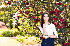 Young beautiful woman with long straight dark hair posing in spr. Ing garden Stock Images