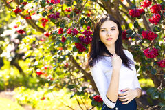Young beautiful woman with long straight dark hair posing in spr. Ing garden Stock Photo