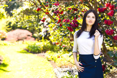 Young beautiful woman with long straight dark hair posing in spr. Ing garden Royalty Free Stock Photos
