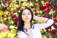 Young beautiful woman with long straight dark hair posing in spr. Ing garden Stock Photography