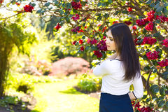 Young beautiful woman with long straight dark hair posing in spr. Ing garden Royalty Free Stock Photography