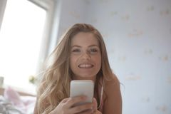 Portrait of cheerful positive girl sitting on bed using smart phone headset listening favorite music enjoying recreation at home royalty free stock image