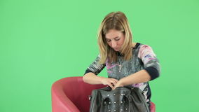 Young beautiful woman looking in her  purse stock footage