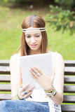 Young beautiful woman looking message in tablet computer, outdoo Stock Images
