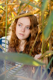 Young beautiful woman looking out of reed Stock Photo
