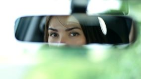 Young beautiful woman looking in rearview mirror stock video