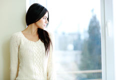 Young beautiful woman looking at window. Portrait of a young beautiful woman looking at window Stock Images