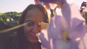 Young beautiful woman looks in flowers outdoor at sunset through the sun in slow motion with lense flare effects stock footage