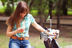Young beautiful woman looks in your phone sitting on the scooter Stock Images