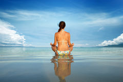 Young beautiful woman in a lotus position. Young beautiful woman in a lotus position on a background of blue sky and island Royalty Free Stock Photography