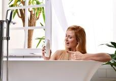 Woman lying in bathtub taking bath near open bathroom window and wash hand with soft shower gel cream lotion. Young beautiful woman lying in bathtub taking bath royalty free stock image