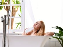 Woman lying in bathtub  taking bath near open bathroom window  and wash hand with soft shower gel cream lotion. Young beautiful woman lying in bathtub  taking Stock Photography