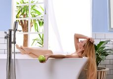 Young beautiful woman lying in bathtub and taking bath near open bathroom window. Tropical resort and spa hold green apple looking up stock photography