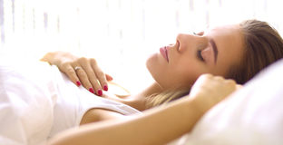 Young beautiful woman lying in bed Royalty Free Stock Images