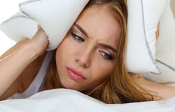 Young beautiful woman lying in bed suffering with insomnia. Covering head and ears with pillow and making unpleasant face. Noisy neighbour, stress, alarm sound Royalty Free Stock Photography