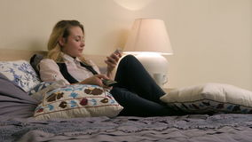 Young beautiful woman lying on the bed, turning on TV channels and using smartphone at home. Professional shot in 4K resolution. 072. You can use it e.g. in stock video