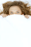 Young beautiful woman lying in bed under blanket Stock Photos