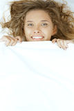 Young beautiful woman lying in bed under blanket Royalty Free Stock Images