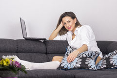 Young beautiful woman lying on a bed and using laptop Royalty Free Stock Photo