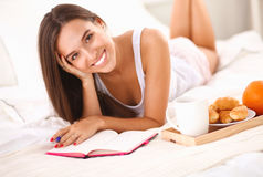 Young beautiful woman lying in bed writing a diary Royalty Free Stock Image