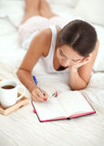 Young beautiful woman lying in bed writing a diary Royalty Free Stock Photos