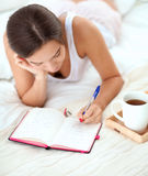 Young beautiful woman lying in bed writing a diary Royalty Free Stock Photography