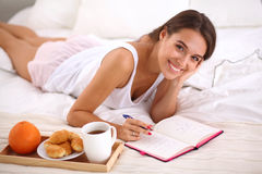 Young beautiful woman lying in bed writing a diary Stock Image
