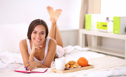 Young beautiful woman lying in bed writing a diary Stock Photo