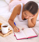 Young beautiful woman lying in bed writing a diary Stock Images