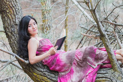 Young beautiful woman lying on a branch of a tree with book Stock Photo