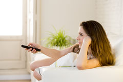 Young beautiful woman lying on couch holding remote control watching television happy and relaxed Stock Image