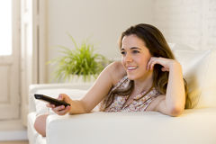 Young beautiful woman lying on couch holding remote control watching television happy and relaxed Stock Photography