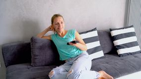 Young, beautiful woman lying on the couch and watching TV. She switches on the remote indefinitely, tracking shot. Young beautiful woman sits on the couch and stock footage