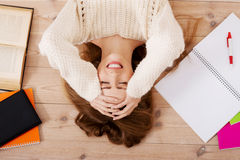 Young beautiful woman lying on the floor with books. Stock Photos
