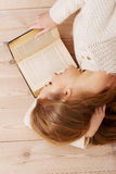 Young beautiful woman lying on the floor with books. Stock Photography
