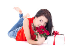 Young beautiful woman lying with gift box and flowers isolated o Royalty Free Stock Photography