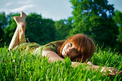 Young beautiful woman lying on grass Stock Image