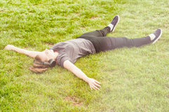 Young beautiful woman lying on grass with arms wide open Stock Image