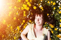 Young beautiful woman lying on grass full of spring flowers, relaxing Stock Photo