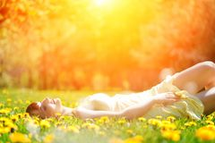 Young beautiful woman lying on grass full of spring flowers, relaxing Stock Image