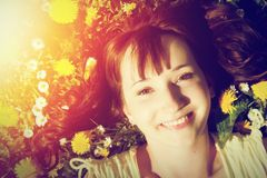 Young beautiful woman lying on grass full of spring flowers and smiling. Royalty Free Stock Image