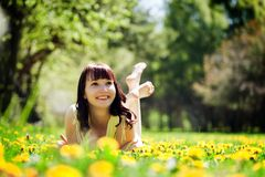 Young beautiful woman lying on grass, smiling Stock Photos