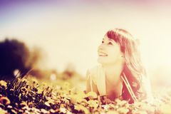 Young beautiful woman lying on grass. Vintage Stock Image