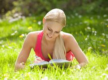 Young Beautiful Woman Lying On Grass Writing In Diary Stock Photo