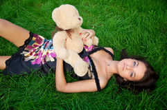 Young beautiful woman lying on a green grass Royalty Free Stock Image
