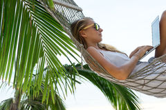 Young beautiful woman lying in a hammock with laptop. Young beautiful woman lying in a hammock with laptop in a tropical Royalty Free Stock Photo