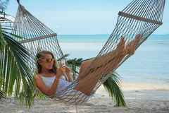 Young beautiful woman lying in a hammock with laptop. Young beautiful woman lying in a hammock with laptop in a tropical Royalty Free Stock Images